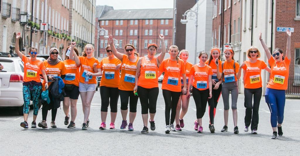 Mini marathon runners lined across the street cheering