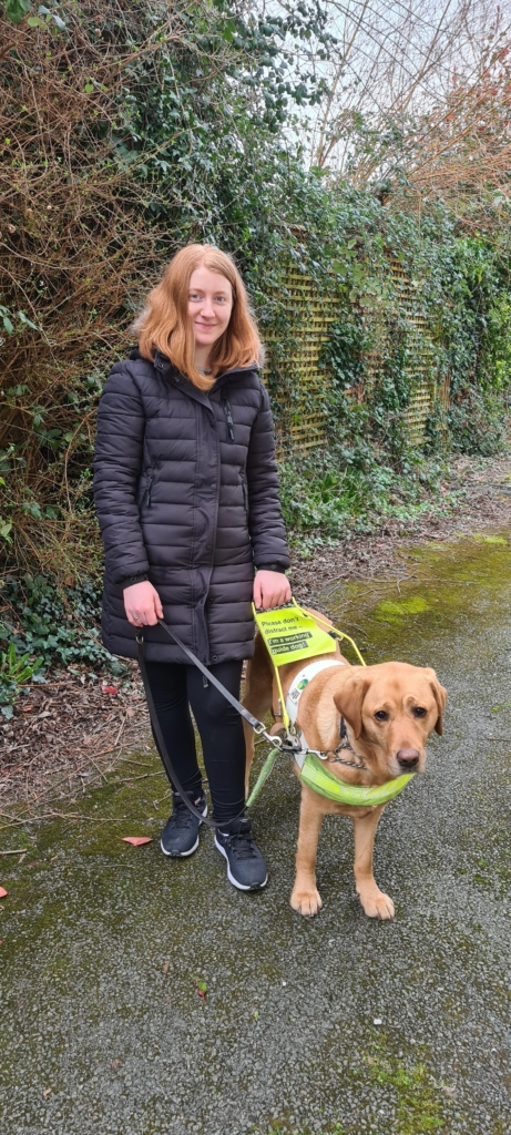 Helena Mollaghan standing with her guide dog
